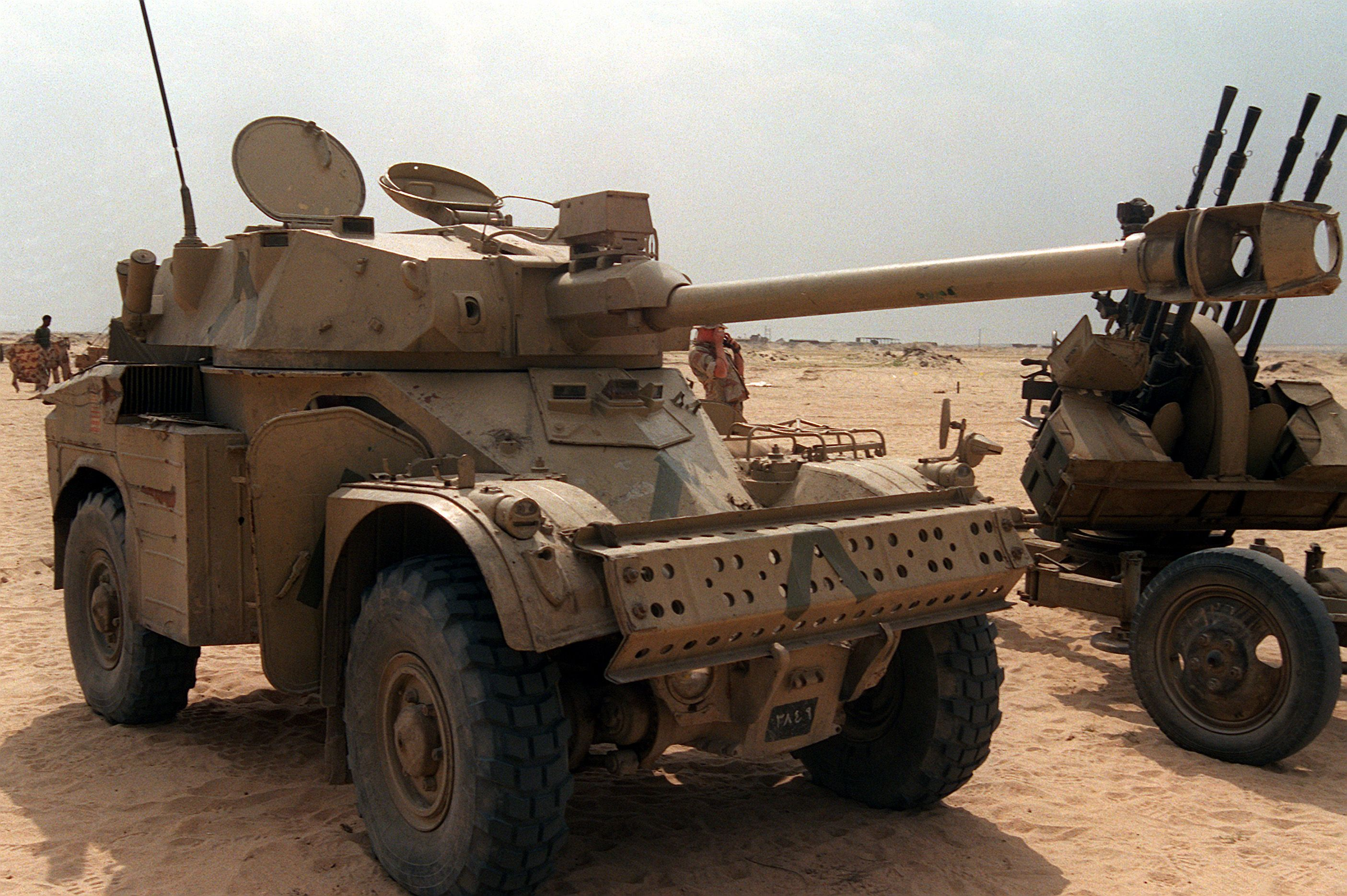 "A right front view of an Iraqi AML-90 light armored car that was captured during Operation Desert Storm.  Inverted ""V"" markings like those used on coalition vehicles have been placed on the vehicle's hull and turret.  A captured ZPU-4 anti-aircraft machine gun is at right."